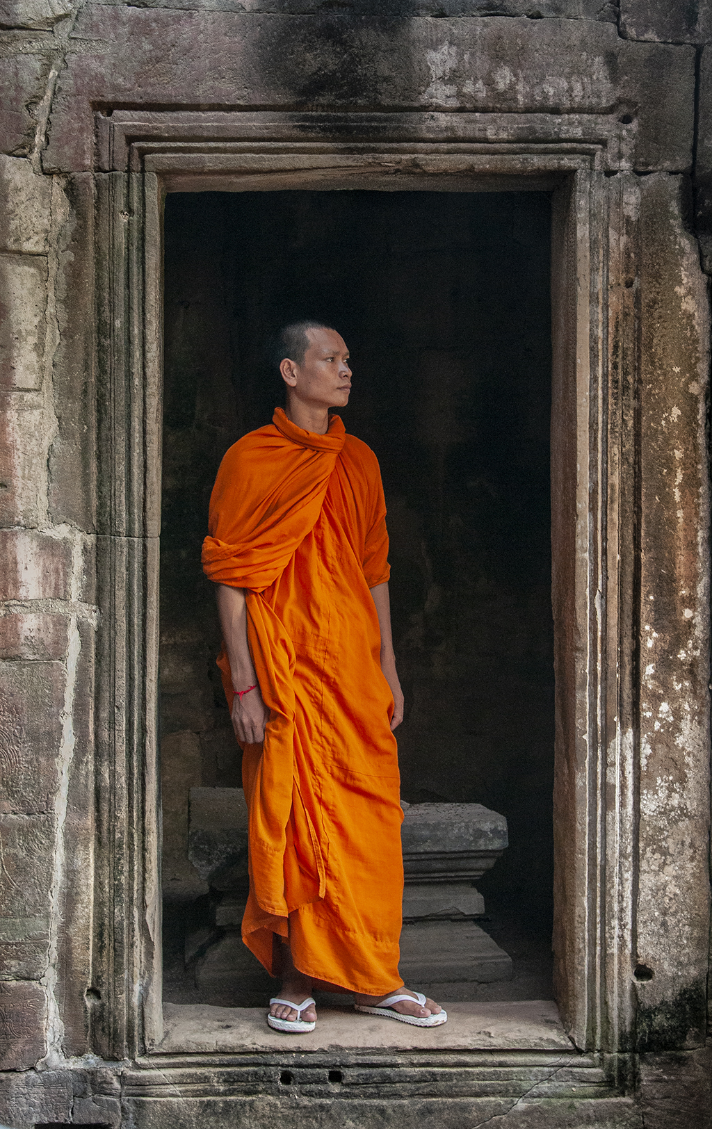 Doorways and windows can provide intriguing compositional elements to frame your subjects, like in this image of a monk from Cambodia.