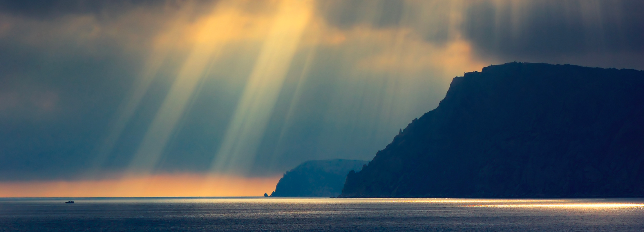 Photo of stormy weather with the sun breaking through over the ocean
