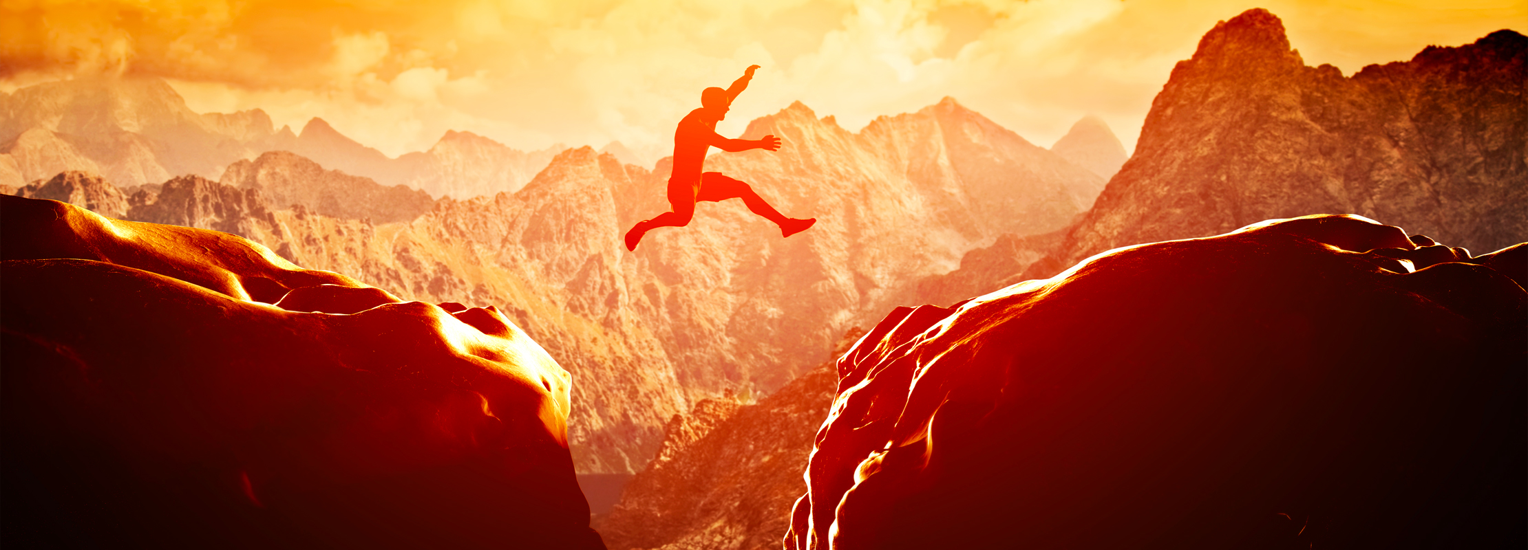 Image of a man jumping between two rocks.